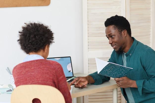 Afrikaanse tutor die het onderwerp aan de jongen uitlegt terwijl ze aan het bureau in de kamer thuis zitten
