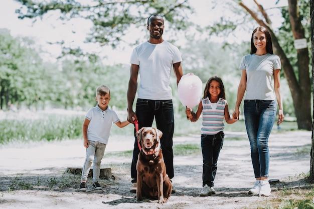 Afrikaanse vader en kaukasische moeder kinderen lopen door park.