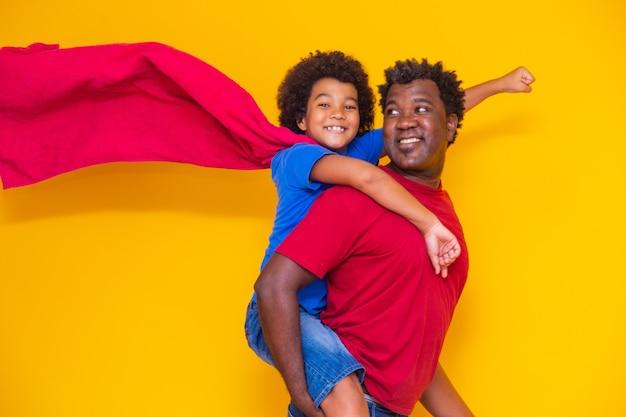 Afrikaanse vader en zoon die overdag superheld spelen. mensen met plezier gele achtergrond. concept van vriendelijke familie.