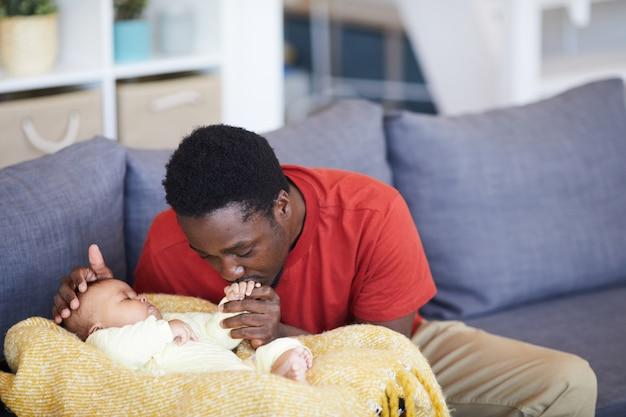 Afrikaanse vader kuste de hand van pasgeboren terwijl hij slaapt, ze zijn in de huiskamer thuis