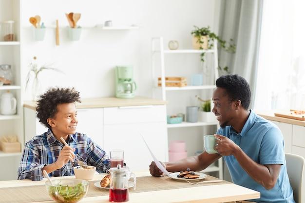Afrikaanse vader praat met zijn zoon terwijl ze aan tafel zitten en thuis ontbijten in de keuken