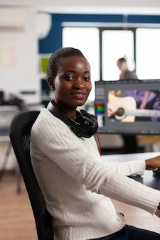 Afrikaanse video-editor die naar een camera kijkt die lacht om een videoproject te bewerken in postproductiesoftware die in een creatief studiokantoor werkt