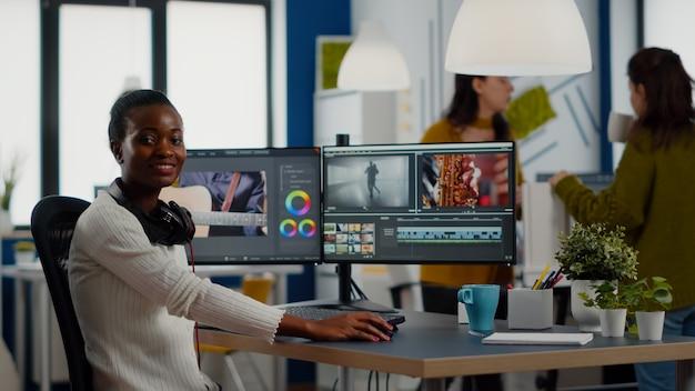 Afrikaanse video-editor kijkt naar camera die lacht en videoproject bewerkt in postproductiesoftware w