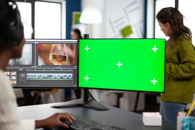 Afrikaanse video-editor met headset die beeldmateriaal bewerkt met pc met groen scherm