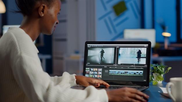 Afrikaanse videograaf die op laptop werkt vanuit kantoor
