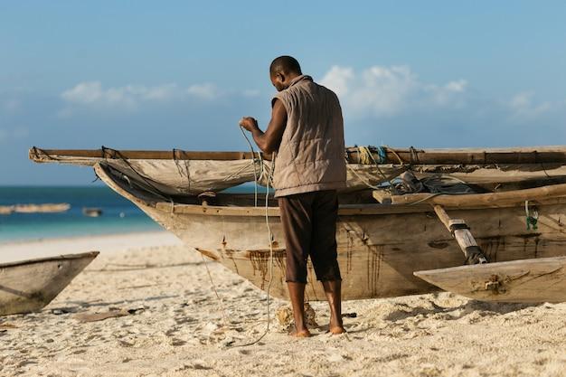 Afrikaanse visser die zijn oude houten boot herstelt