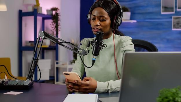 Afrikaanse vlogger die videoblog opneemt en berichten leest van smartphone met moderne apparatuur in studiopodcast