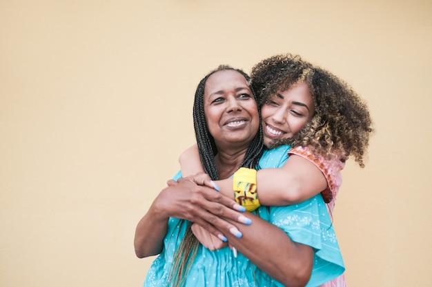 Afrikaanse volwassen dochter knuffelt haar moeder terwijl ze traditionele kleding draagt - familieliefde
