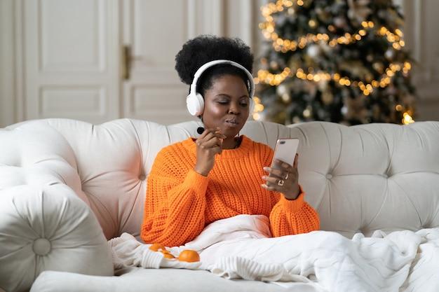 Afrikaanse vrouw brengt kerstochtend thuis door in de woonkamer met kerstboom en leest sms in smartphone