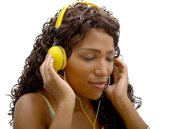 Afrikaanse vrouw die aan muziek luistert