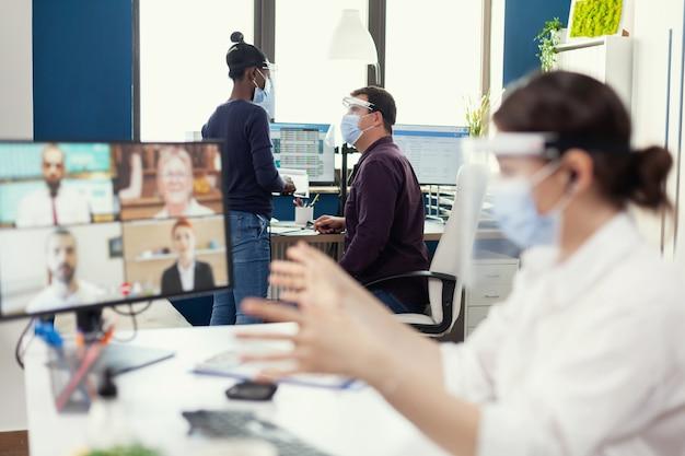 Afrikaanse vrouw die een gesprek voert met haar collega die een gezichtsmasker draagt op de werkplek met een gezichtsmasker. ondernemer met videogesprek terwijl collega's werken met respect voor sociale afstand tijdens wereldwijde p