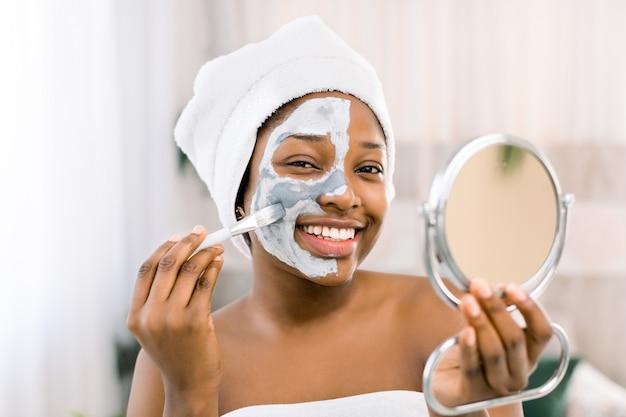 Afrikaanse vrouw die een handdoek, met gezichtsmasker draagt. close-up die van afrikaanse vrouw gezichtsmasker in kuuroord toepassen