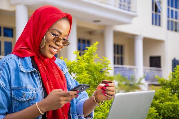 Afrikaanse vrouw die gelukkig online winkelt met behulp van een laptop en een smartphone terwijl ze haar creditcard vasthoudt