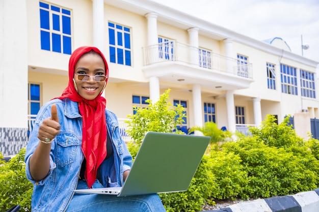 Afrikaanse vrouw die hetzelfde teken gebaart terwijl ze in het park zit met haar laptop