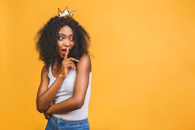 Afrikaanse vrouw die in vrijetijdskleding wijsvinger op lippen houdt en vraagt om stilte te bewaren