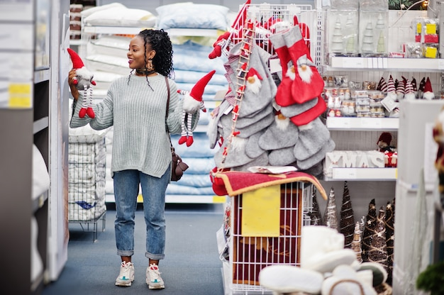 Afrikaanse vrouw die nieuwe jaardingen kiest voor haar flat in een moderne woninginrichtingopslag. kerstthema winkelen.