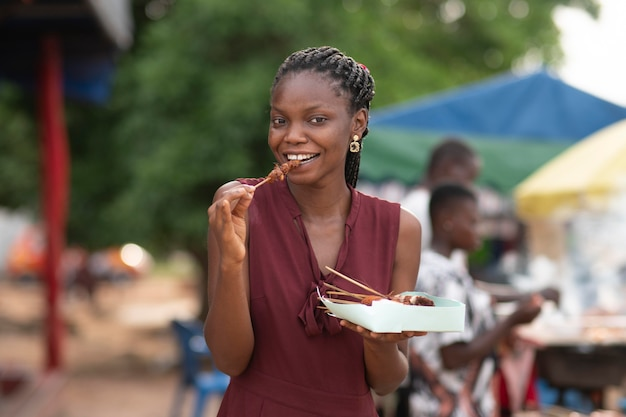 Afrikaanse vrouw die straatvoedsel eet