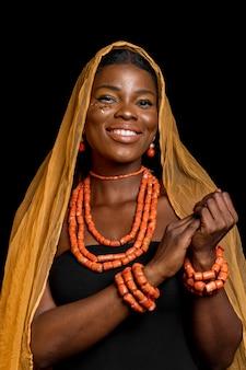 Afrikaanse vrouw die traditionele accessoires en gele sluier draagt