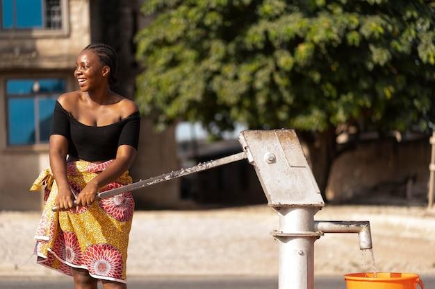 Afrikaanse vrouw die water in een recipiënt giet