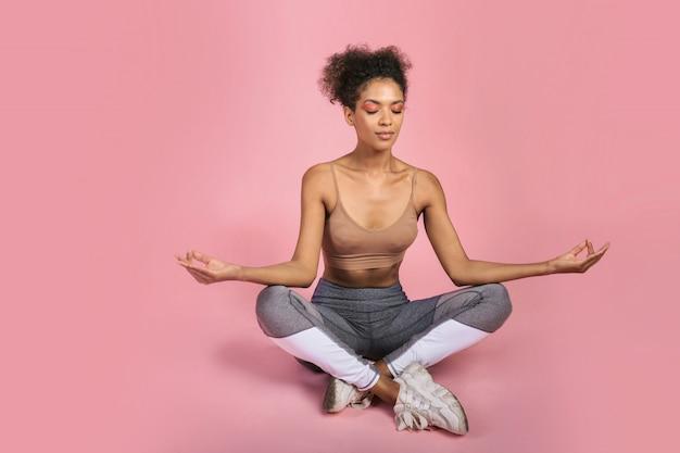 Afrikaanse vrouw die yoga in studio doet. roze achtergrond.