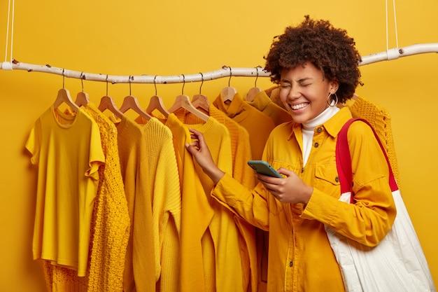 Afrikaanse vrouw gekleed in een stijlvolle gele jas, draagt boodschappentas, mobiele telefoon gebruikt voor online communicatie, vormt in de buurt van kledingrail tegen gele achtergrond