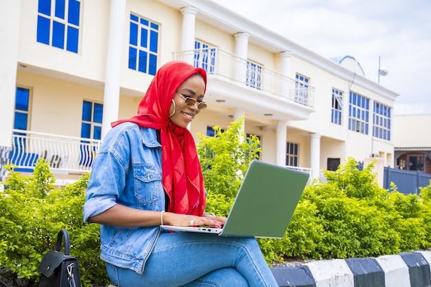 Afrikaanse vrouw gelukkig online browsen met behulp van een laptop zittend in een park