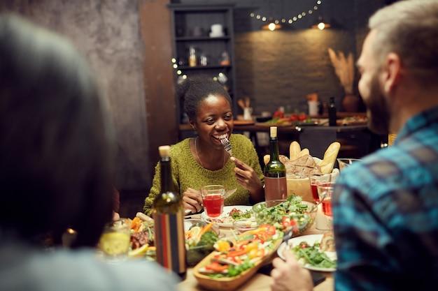 Afrikaanse vrouw genieten van diner met vrienden