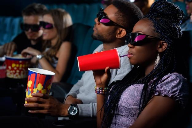 Afrikaanse vrouw genieten van haar drankje op een date met haar man in de bioscoop