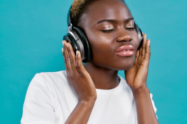 Afrikaanse vrouw het luisteren muziek met dicht omhoog hoofdtelefoons.