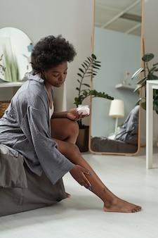 Afrikaanse vrouw in grijze homewear die crème op benen aanbrengt