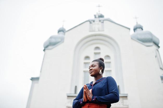 Afrikaanse vrouw in oranje broek en blauw shirt gesteld tegen grote kerk