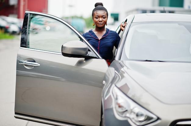 Afrikaanse vrouw in oranje broek en blauw shirt gesteld tegen zilveren suv auto met geopende deur