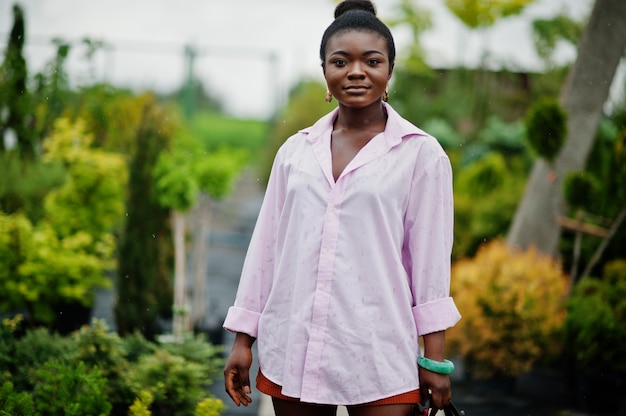 Afrikaanse vrouw in roze groot overhemd gesteld op tuin met zaailingen.