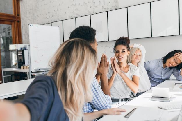 Afrikaanse vrouw in t-shirt spelen met collega in grappig spel op kantoor. aantrekkelijke jonge vrouwelijke werknemer gek rond met zwarte man tijdens bijeenkomst in conferentiezaal.