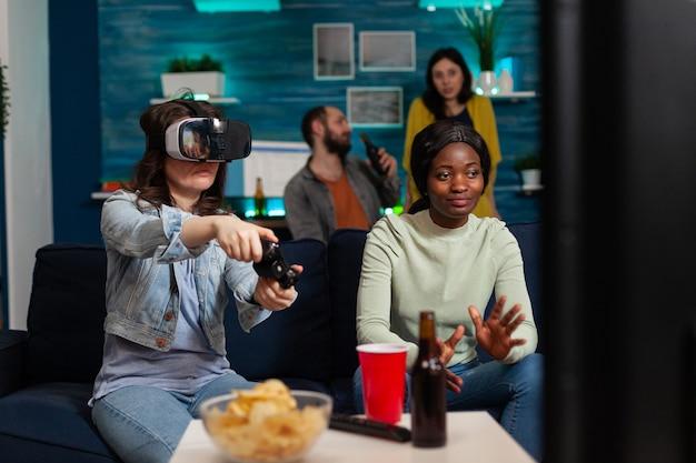 Afrikaanse vrouw juicht voor vrienden tijdens videogamecompetitie met een virtual reality-bril die op de bank zit en plezier heeft, met behulp van een draadloze controller. gemengd ras groep mensen socialiseren.