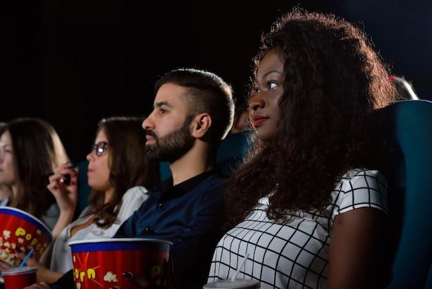 Afrikaanse vrouw kijken naar een film met haar vrienden in de plaatselijke bioscoop