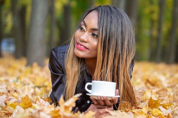 Afrikaanse vrouw koffie drinken uit een witte beker op de achtergrond van de herfstbladeren in het park
