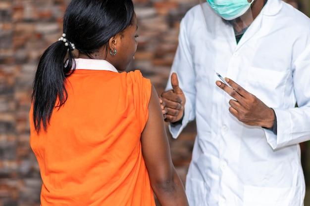 Afrikaanse vrouw krijgt een duim omhoog van medisch personeel na ontvangst van een vaccin
