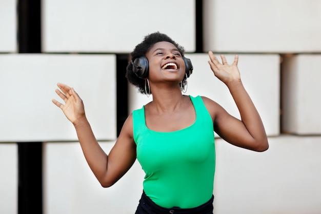Afrikaanse vrouw lacht, luistert naar muziek met een koptelefoon en danst op straat.