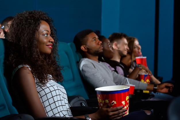 Afrikaanse vrouw lacht vrolijk terwijl u geniet van haar tijd in de bioscoop