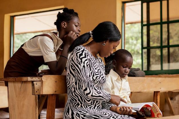 Afrikaanse vrouw lesgeven aan kinderen in de klas