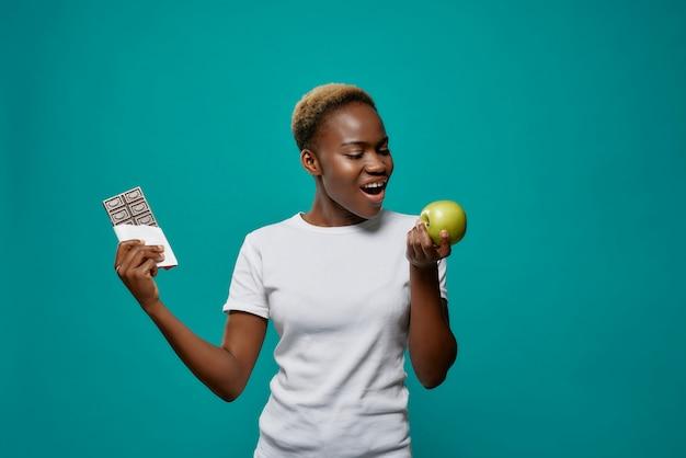 Afrikaanse vrouw met appel en donkere chocoladereep.