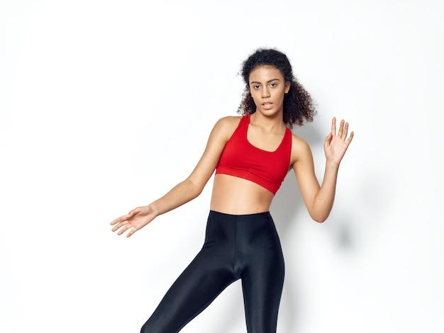 Afrikaanse vrouw met donkere huid poseren in een trainingspak en sporten in de studio