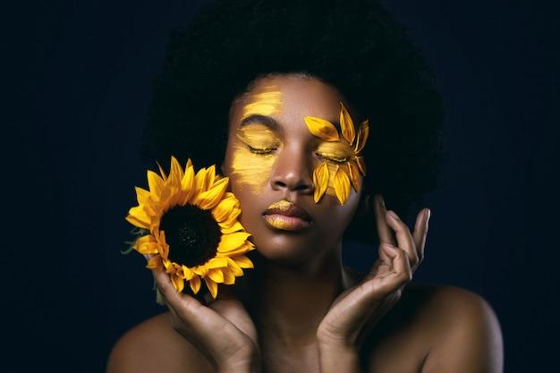 Afrikaanse vrouw met een zonnebloem en creatieve make-up op haar gezicht