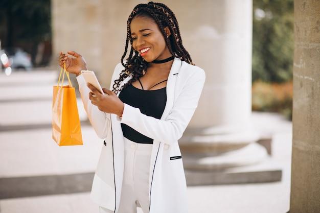 Afrikaanse vrouw met gele boodschappentassen