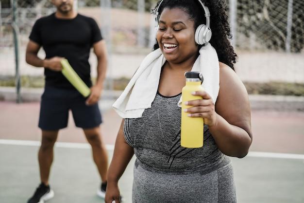 Afrikaanse vrouw met grote maten die ochtendroutine buiten doet in het stadspark - focus on girl face
