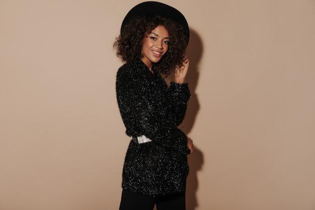 Afrikaanse vrouw met kort krullend kapsel in zwarte hoed en stijlvolle glanzende kleding glimlachend en kijkend naar de camera op beige muur..