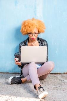Afrikaanse vrouw met krullend haar die met laptop werkt die op de blauwe muurachtergrond zit