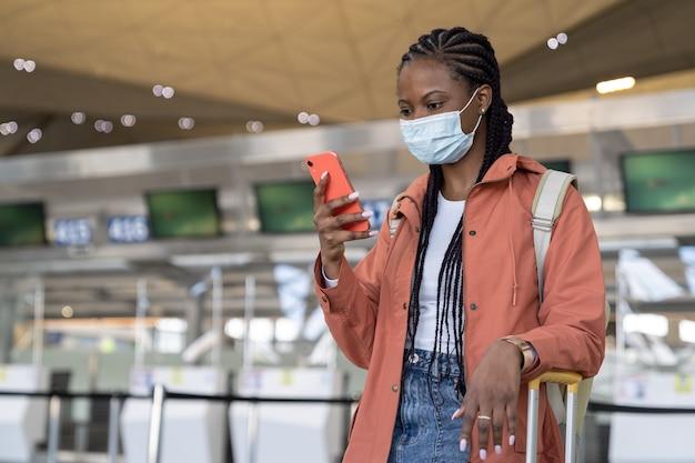 Afrikaanse vrouw met smartphone draagt gezichtsmasker op de luchthaven