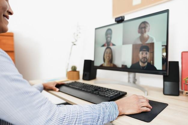 Afrikaanse vrouw met video-oproep met haar collega's met behulp van computer-app - focus op rechterhand
